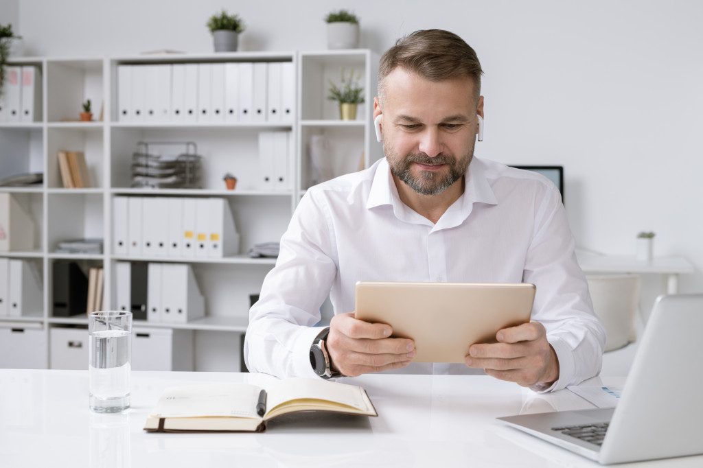 Serious businessman with touchpad watching online video training or conference