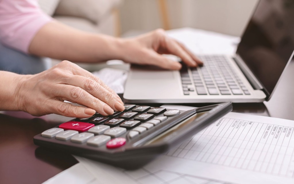 senior-woman-with-calculator-counting-dollar-money-QTZBNJ2 red